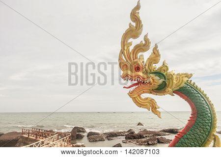 Naga Head Statue On Seashore At Cloudscape Background.