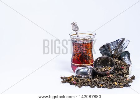 Typical Turkish glass for tea with a teaspoon and tea inside and an open infuser with mango green tea on a white background