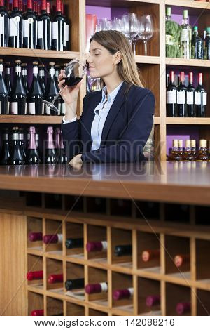 Mid Adult Customer Smelling Red Wine Against Shelves