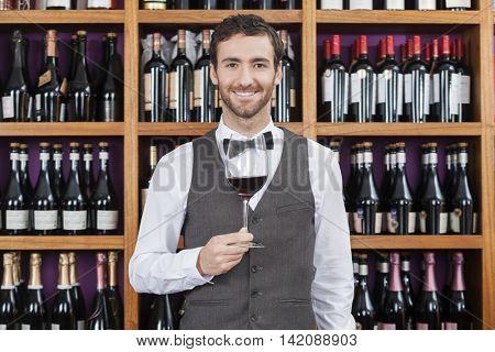 Bartender Holding Red Wine Glass Against Shelves