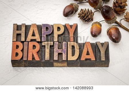 Happy Birthday greeting card - text in vintage letterpress wood type against white Nepalese lokta paper with cone and acorn fall decoration