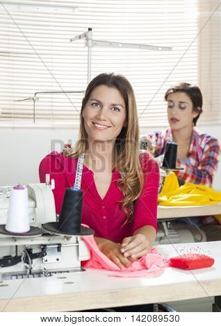 Happy Female Tailor Sitting At Workbench