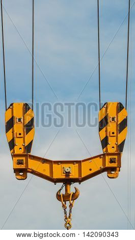 Bright orange tower crane against of blue sky , hook detail, construction concept, vertical