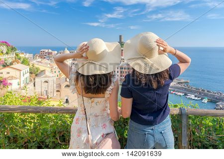 Two girls in hats looking at the village of Vernazza from the hill. Italy. Liguria. Cinque Terre.