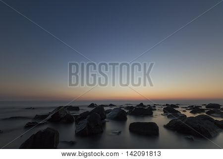 Sunset over the coast with stones with blurred water