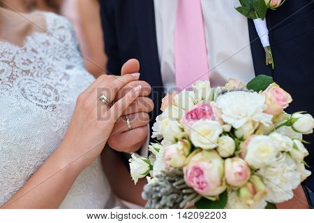 bride and groom holding hands with bridal bouquet.
