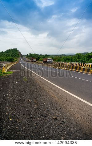 Long stretch of empty road bordered with tree filled hills and under beautiful monsoon skies. Showing a great way to explore india via the well developed road network