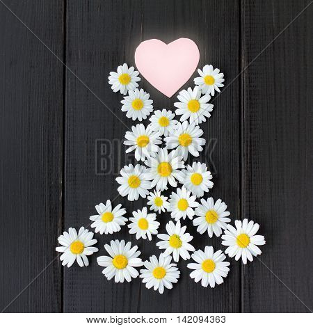 flat lay of your favorite summer dress daisies with heart symbol on wooden background / fashionable floral dress from your favorite collection