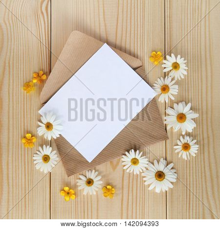 background with daisies and a flat layout about an open letter to the unfilled card top view / letter with floral mood