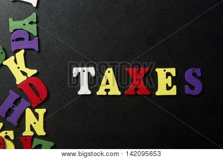 Word of TAXES spelled with colorful wooden alphabet letters.