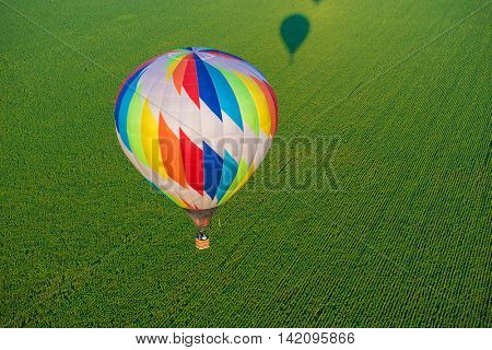 Hot air balloon is flying over the green field