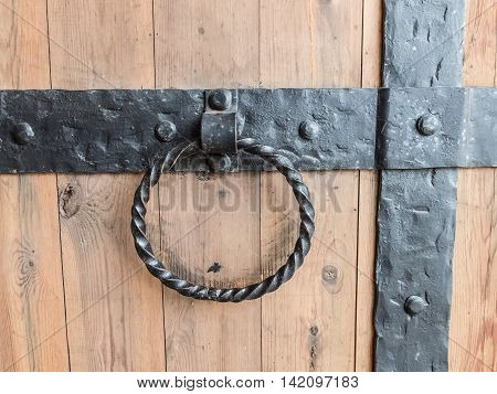 Vintage forged handle gate of the historic fortress. Detail of the doors of the Tikhvin monastery in Russia. Strong ancient building to protect the castle.
