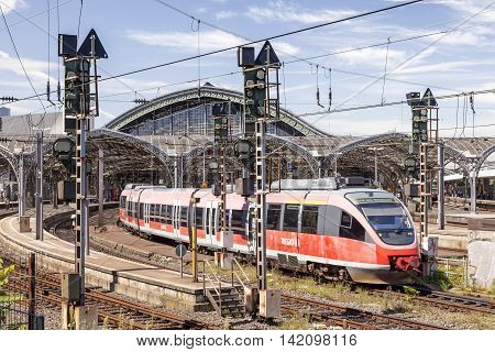 COLOGNE GERMANY - AUG 7 2016: Red passenger train leaving the main train station of Cologne. North Rhine-Westphalia Germany