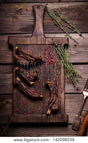 Roasted Meat And Spices On Chopping Board. Dark Wooden Background .
