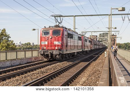 COLOGNE GERMANY - AUG 7 2016: Red Deutsche Bahn train at the South Bridge in Cologne North Rhine-Westphalia Germany