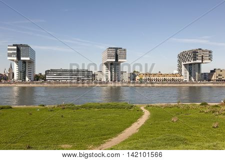 COLOGNE GERMANY - AUG 7 2016: The three modern Crane Houses (german Kranhaus) at the Rhine River in Cologne as seen from opposite river bank