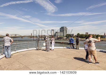 COLOGNE GERMANY - AUG 7 2016: Tourists at the Rhine River promenade with a nice view in the city of Cologne Germany