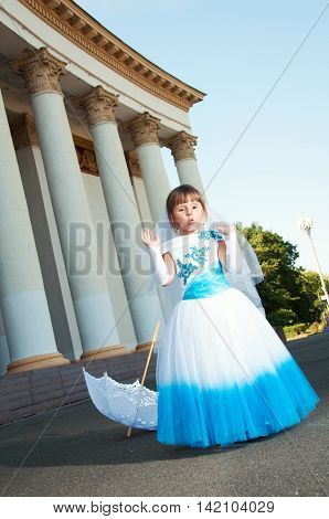 Girl in magnificent blue and white evening dress near the colonnade