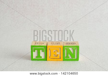 The word ten (10) spelled with colorful alphabet blocks isolated against a white background