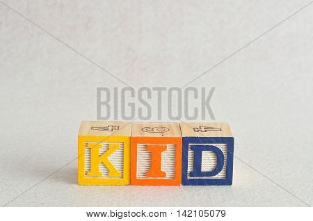 The word kid spelled with alphabet blocks isolated on a white background