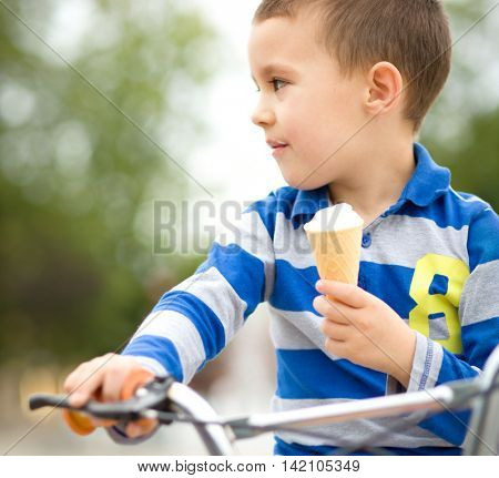 Little boy is eating ice-cream while sitting on bike, outdoor shoot