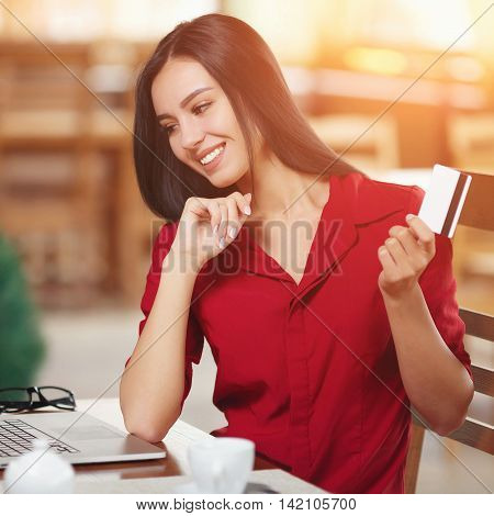 Business woman pays for a purchase with credit card. Beautiful girl in red shirt makes a purchase on the Internet. Buy and shopping online.