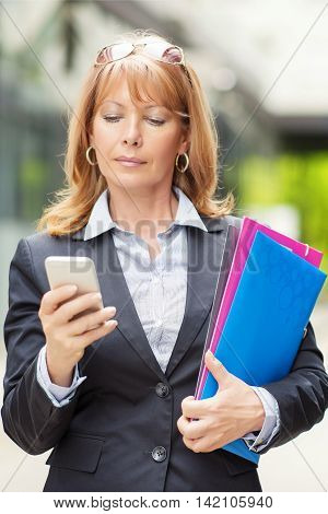 Businesswoman with smart phone.Businesswoman standing in front of an office building and reading text message.