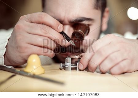 Close up portrait of a watchmaker at work.A watchmaker or repair man in action viewing very closely a swiss watch.