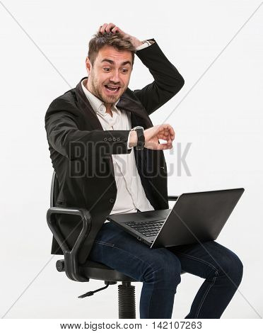 Tired manager sitting on a chair working with a laptop in a panic looking at his watch on his right hand holding his head with his left hand. Studio, white background.