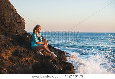 Young blond woman tourist in blue shirt and jeans shorts sittig on rocks by the sea at sunset with bottle of lemonade, looking at horizon and smiling. Kleopatra beach, Alanya, Mediterranean region, Turkey.