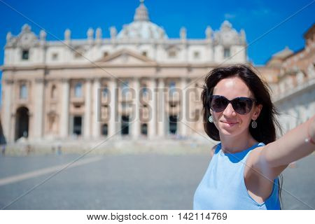 Happy woman taking selfie in Vatican city and St. Peter's Basilica church, Rome, Italy