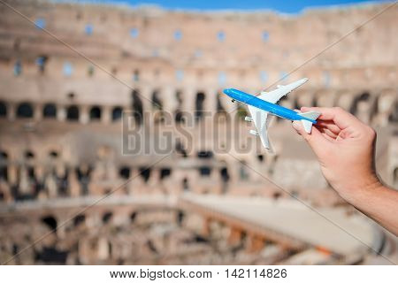 Small airplane model background Coliseum, Rome, Italy