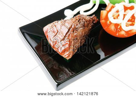 served roast veal fillet on a black plate with tomato
