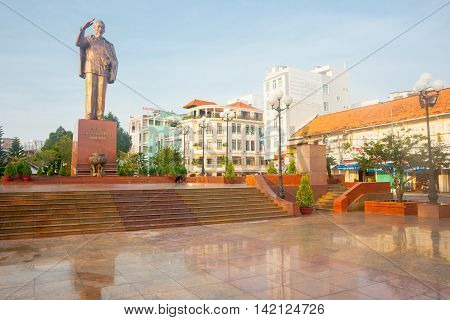 Can Tho, Vietnam - October 16, 2013: Statue remembering Ho Chi Minh saluting mounbted on high plinth overlooking marble clad plza on bank of Mekong River