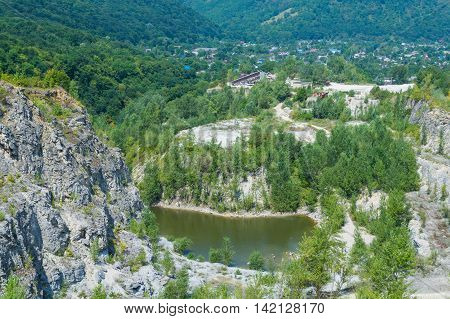 Panorama of abandoned and flooded quarry. Beautiful summer landscape in Adygeya respublic in Russia.