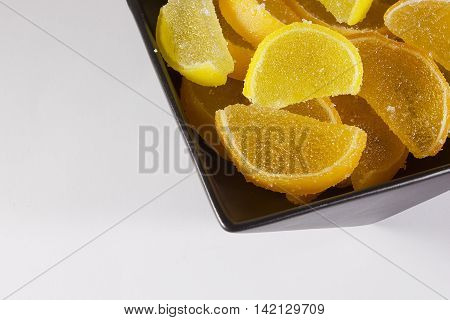 Candy jujube as lemon and orange slices in a black ceramic ware