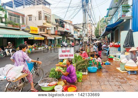 Can Tho Vietnam - October 16, 2013: Street of Vietnamese fruit and vegetable vendors camped on sidewalk in front of shops typicl shop houses on second level.