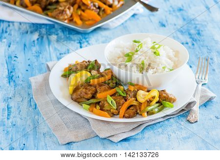 Chicken stir fry with bell peppers and green beans in lemon glaze. Asian style chicken on plate selective focus closeup