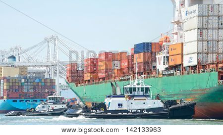 Oakland CA - July 27 2016: Cargo Ships are unable to maneuver sideways. Multiple tugboats push SEASPAN CHIWAN sideways to the dock at the Port of Oakland.