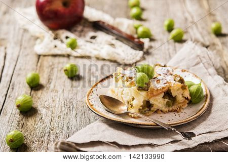 Light pie with fresh berries and fruit. Gooseberries and Apples Pie on a rustic wooden background and homespun cloth. Slice of pie