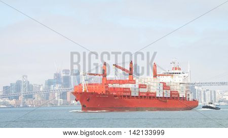 Oakland CA - August 08 2016: Cargo Ship CAP PALMERSTON traveling through the San Francisco Bay en route to the Port of Oakland with Tugboat REVOLUTION at the stern to assist with maneuvering.