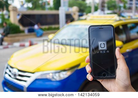 CHIANG MAITHAILAND - JUN 132016 : A MAN hand holding Uber app showing on iphone 6s. Uber is smartphone app-based transportation network