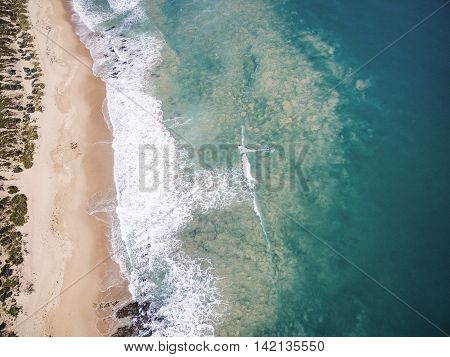 Aerial of beach with surfer riding wave, Western Australia