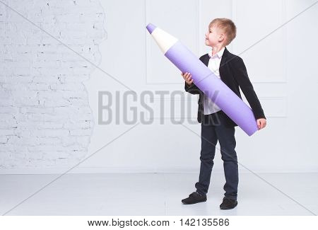 Boy in school uniform holding a big pencil and shows them the way. The concept of the day of knowledge