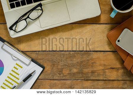 Office desk table with laptop eyeglasses cup of coffee pen leather notebook and chart or graph over backboard. Top view with copy space.