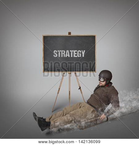 Strategy text on blackboard with businessman sliding with a sledge