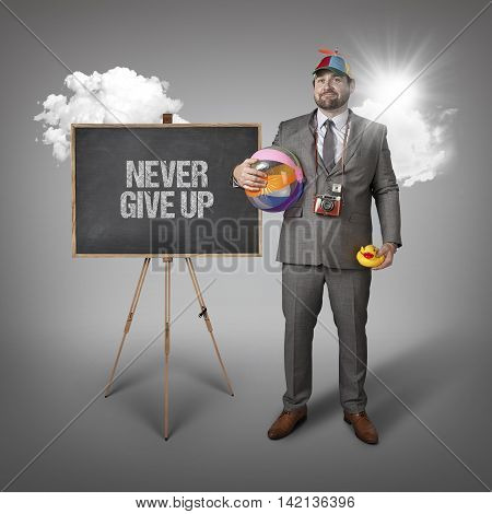 Never give up text with holiday gear businessman and blackboard with text
