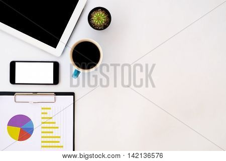 White office desk table with blank screen tablet chart or graph over backboard blank screen smartphone and cup of coffee. Top view with copy space