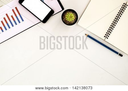 White office workspace with leather notebook blank screen smartphone chart or graph over backboard and pencil. Top view with copy space