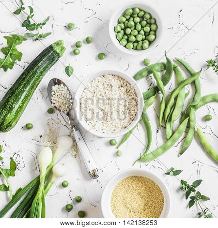 Raw ingredients - rice cous cous zucchini green beans and peas on a light background. Healthy vegetarian food
